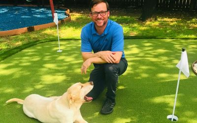 Ideal Turf Customer kneeling on recent backyard putting green installation at his home in Fort Worth Texas