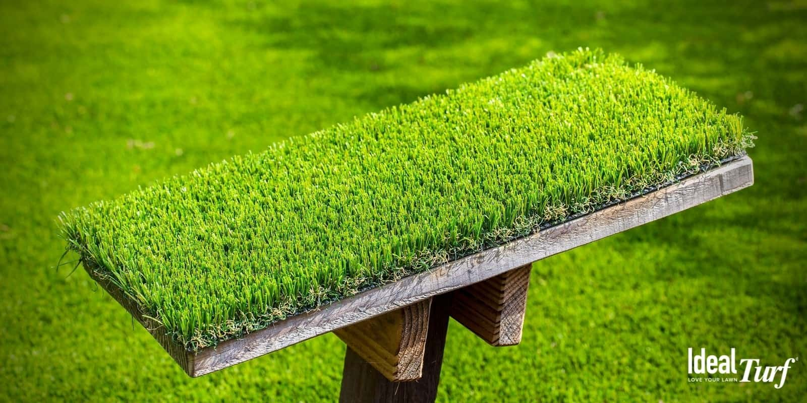 Closeup of turf product sample with artificial grass installation in background