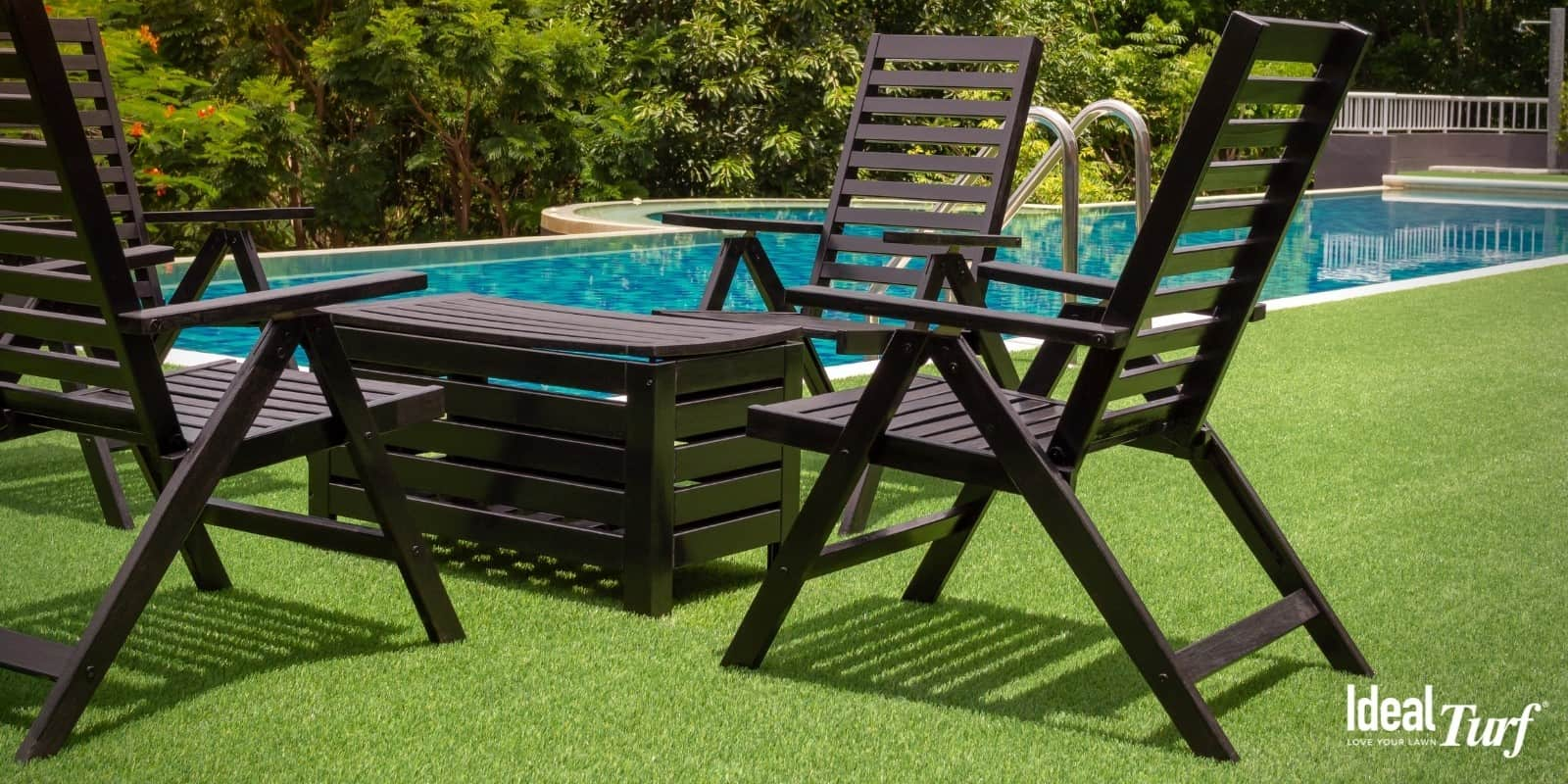 Table and chairs next to pool with artificial grass around it