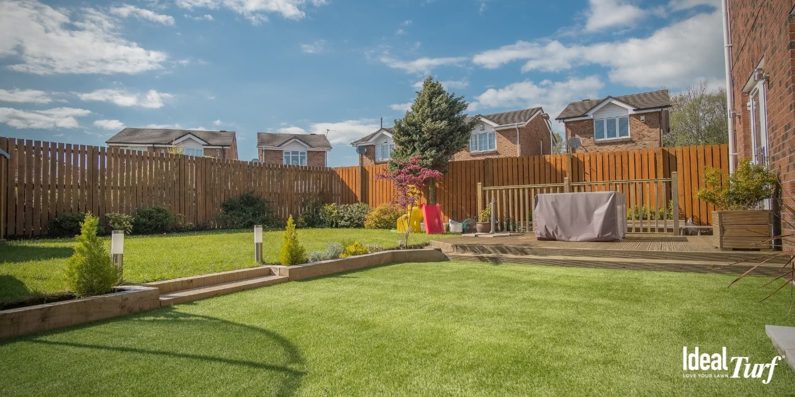 Fenced-in backyard with artificial grass