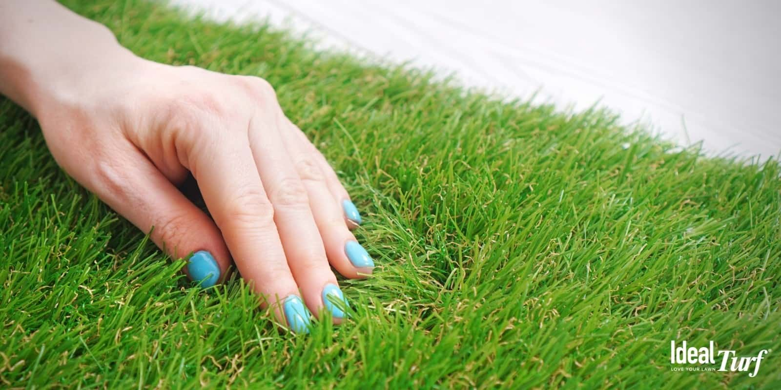 Woman's hand running through artificial grass showing how resilient and springy the fibers are