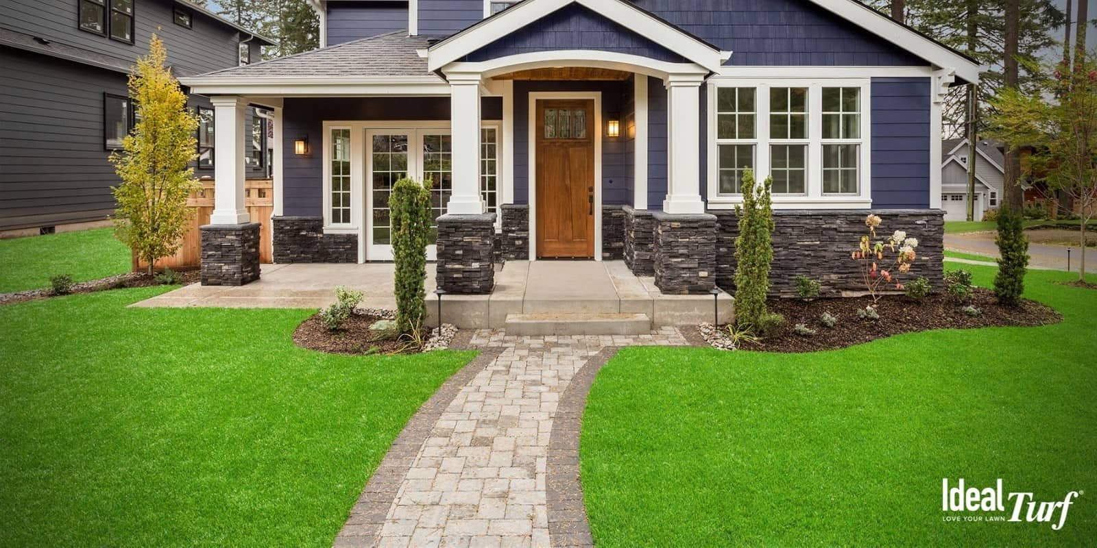 Blue house with the best artificial grass installed in front and sideyard