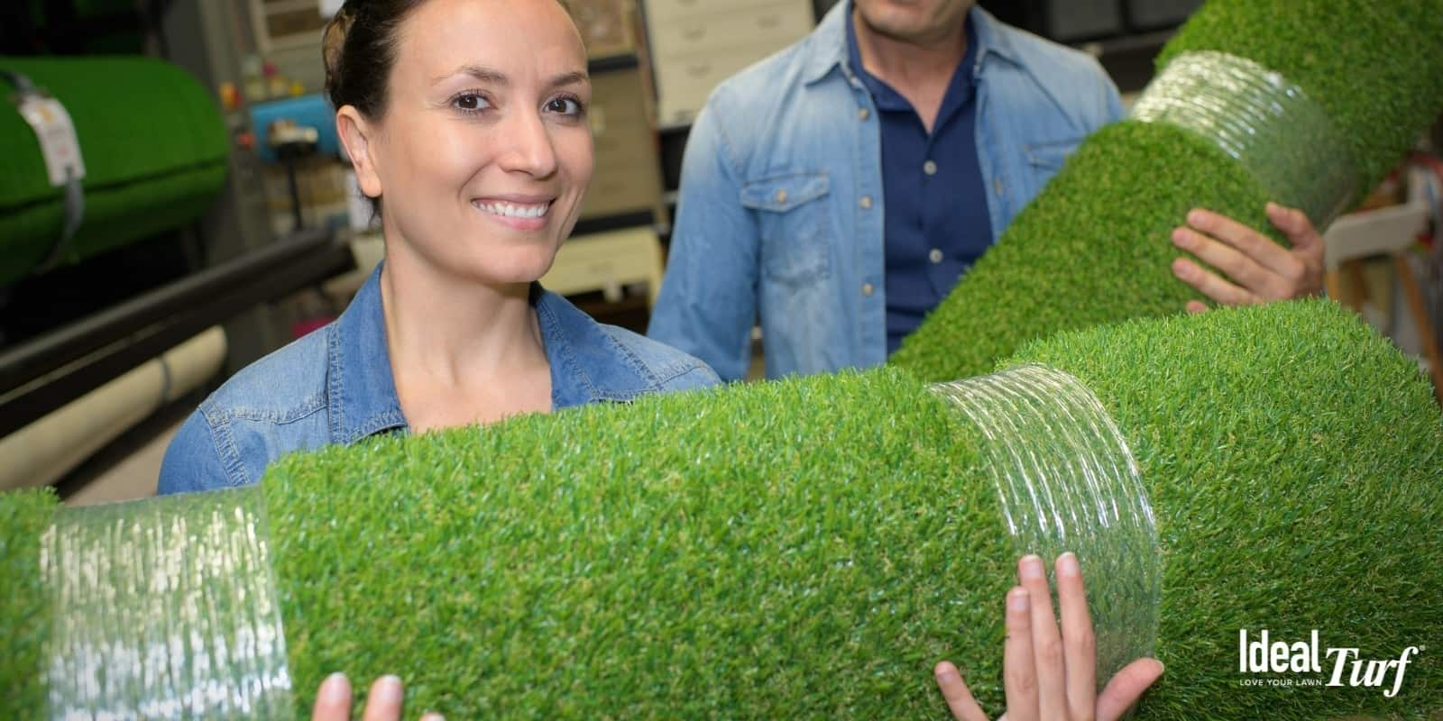 Man and woman carrying rolls of artificial grass
