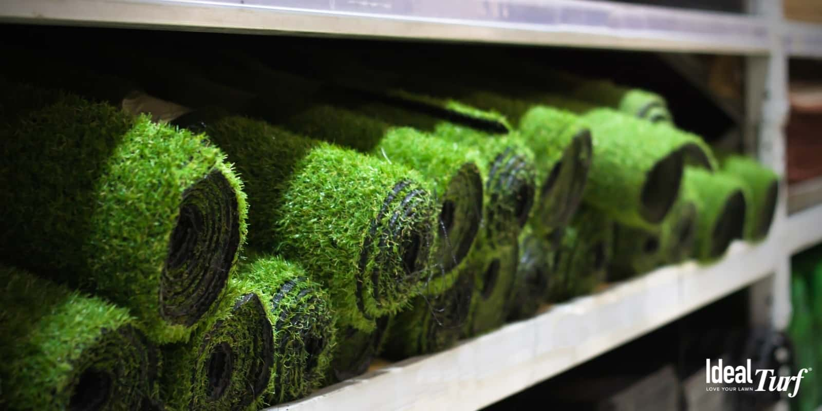 Rolls of artificial grass sitting on shelves in a warehouse