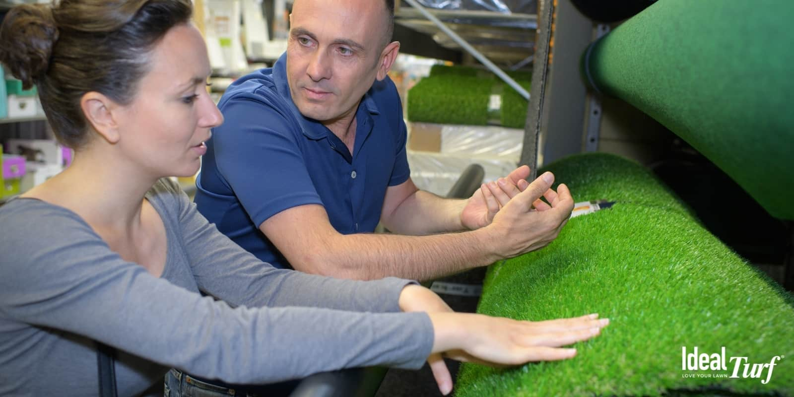 Homeowners looking at rolls of artificial grass