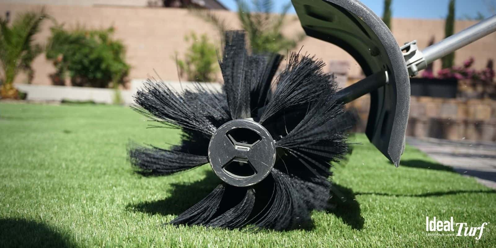 Artificial grass being fluffed with a power broom