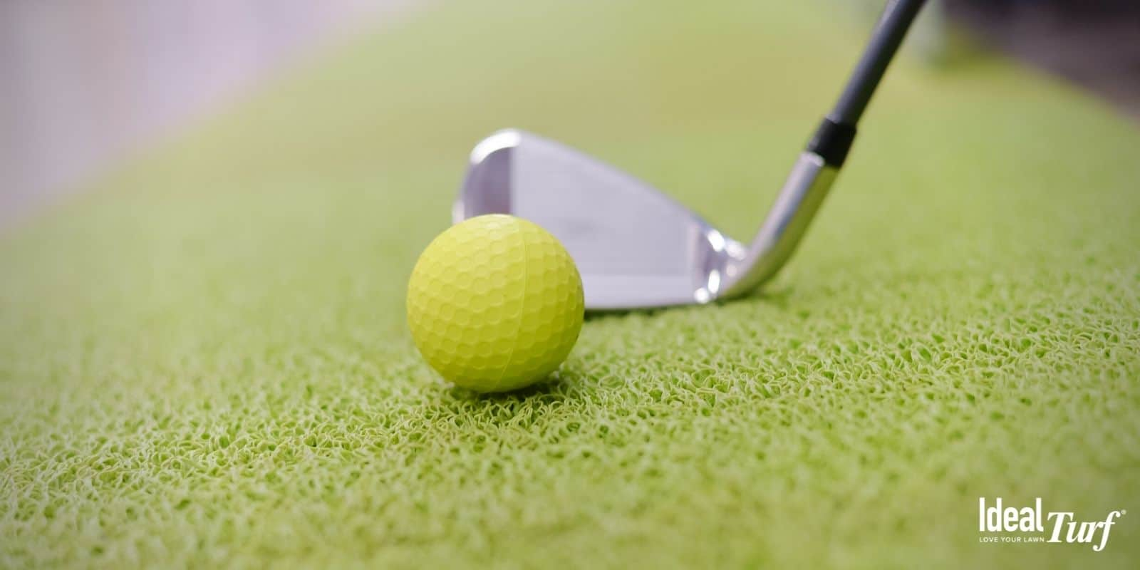 Golf ball sitting on an indoor artificial turf putting green
