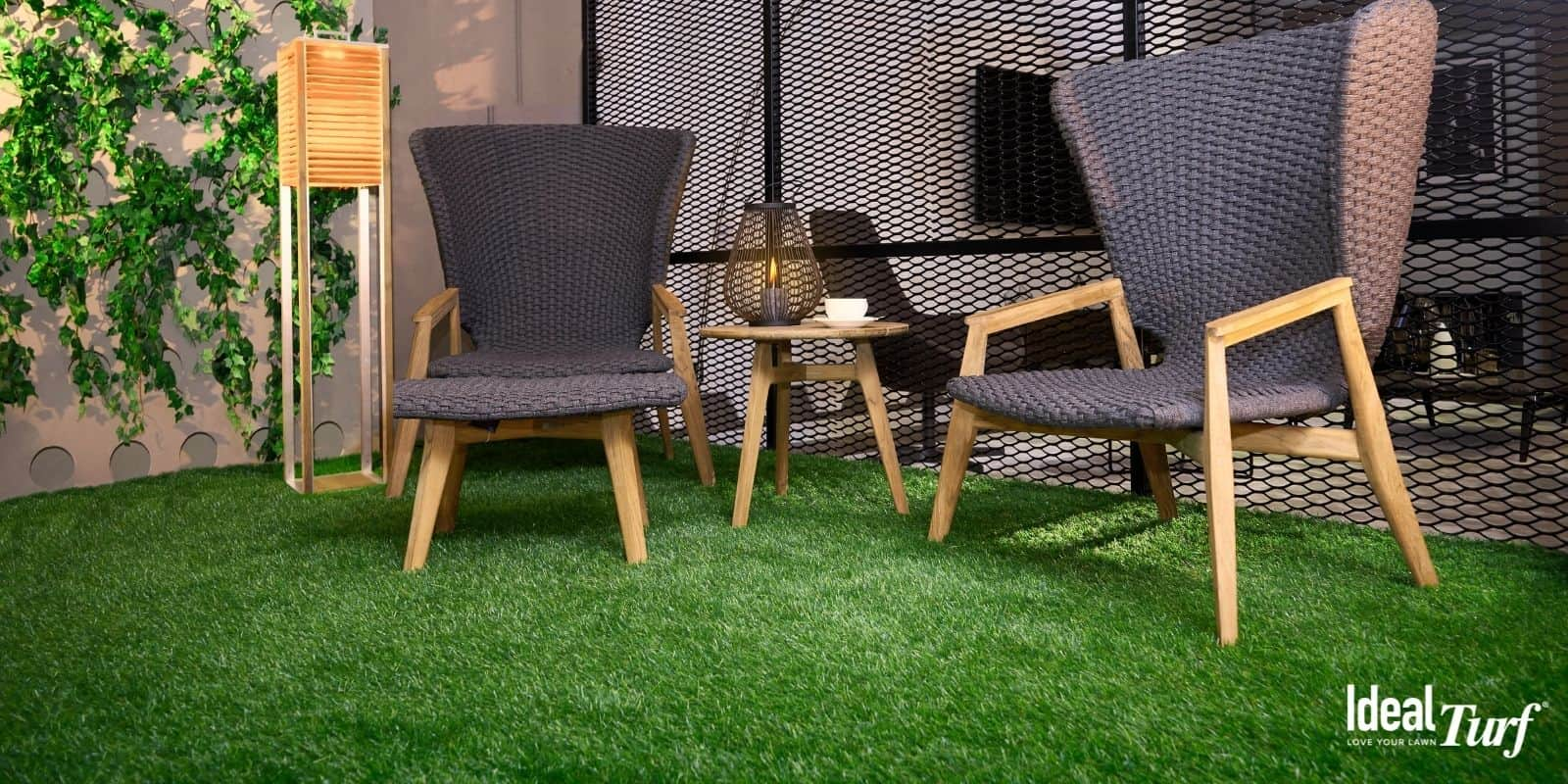 Indoor living space with two black chairs on artificial grass floor covering