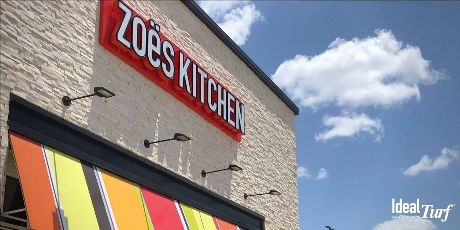 Picture of Zoe's Kitchen sign over multi-colored awning