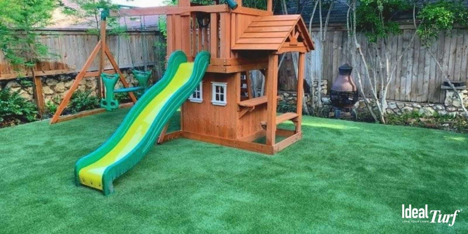 Wooden children's play structure on artificial turf in backyard