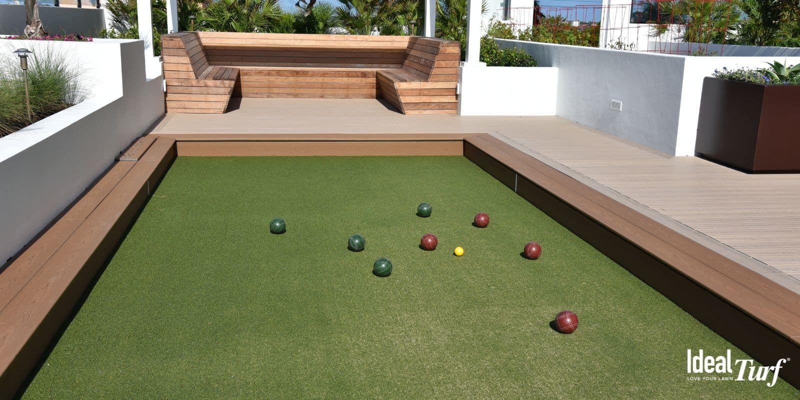 Bocce balls at one end of an artificial turf bocce ball court in backyard