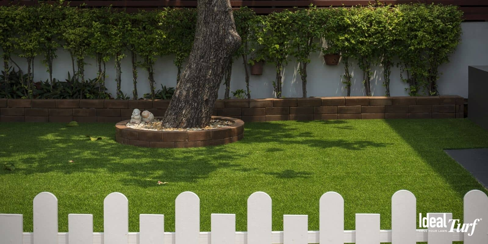 Residential backyard with artificial turf lawn surrounded by white picket fence