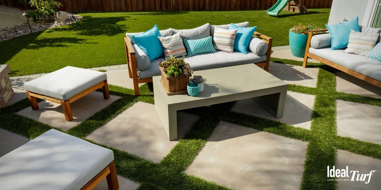 Residential backyard patio area with artificial grass installed between pavers