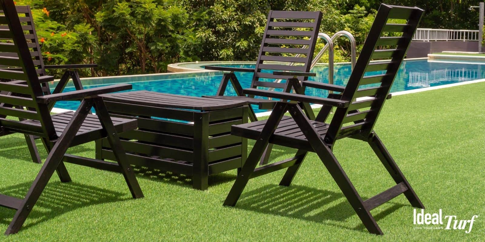 Swimming pool in backyard surrounded by artificial turf